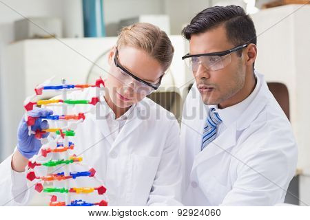 Concentrated scientists working together with dna helix in laboratory poster