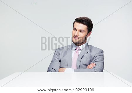 Pensive businessman sitting at the table with arms folded over gray background. Looking away