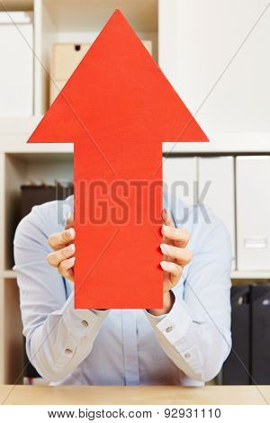 Woman in office holding arrow pointing up with her hands