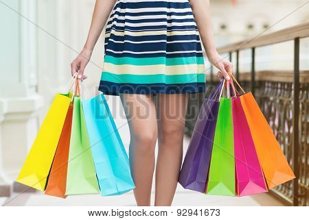 A Woman With A Lot Of Colourful Shopping Bags.