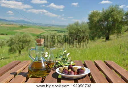 Olive oil and olives and on the wooden table against Tuscan landscape. Italy