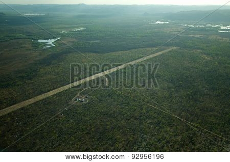A Small Airstrip In Remote Kakadu Np. Northern Territory, Australia is shrouded in thin smoke from a nearby forest fire. poster