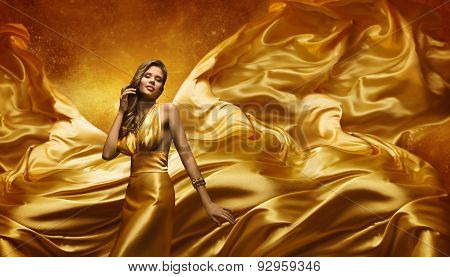 Fashion Model Gold Dress, Beauty Woman Posing Over Flying Waving Cloth, Girl Yellow Silk Fabric