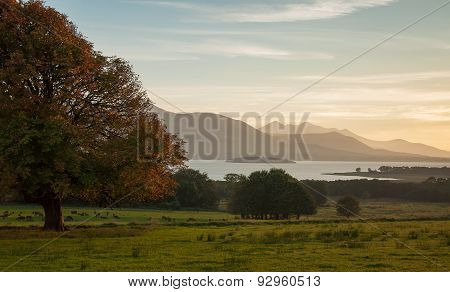 Landscape with meadow,lake and distant mountains at Sunset.