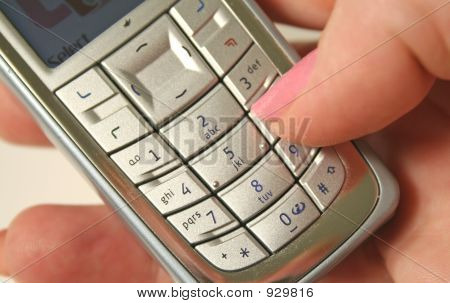 close up of a thumb operating the keyboard of a cell phone. poster
