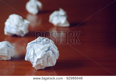 Paper balls over wooden table - Creativity crisis concept