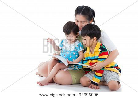 Young Female With Two Little Asian Children Reading A Book
