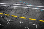 Top view of the asphalt of a car racing pit stop with painted signs and tire marks poster