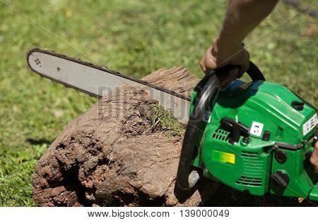 Man cutting piece of wood with chain saw. Blurred background.