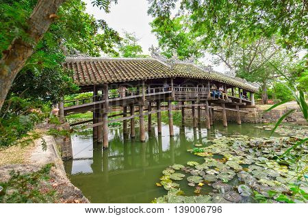 Thua Thien Hue, Vietnam - June 21st, 2015: Architecture bridge with wooden roofing tile structures like a house on river to Attract tourists relax idyllic countryside beauty