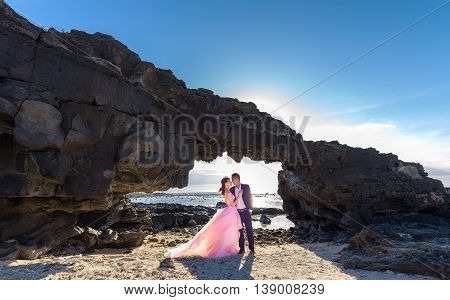 Ly Son Island, Vietnam, June 27th, 2015: Couple happy with stone gate on bay when the afternoon sun gradually to create a halo behind highlighters enjoying holiday island wilderness