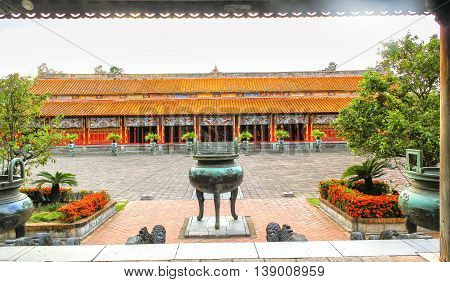 Hue, Vietnam - July 16th, 2011: Entrance the Forbidden City of Hue with a large bronze censer is where worship ceremony praying for peace the country, behind the church of the Kings many generations of feudal and was recognized cultural heritage national