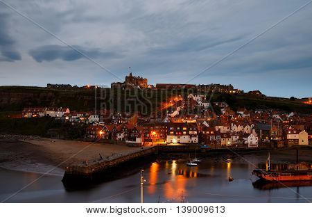 WHITBY ENGLAND - JULY 16: The ruins of Whitby Abbey with the harbour in the foreground at dusk. In Whitby North Yorkshire England. On 16th July 2016.