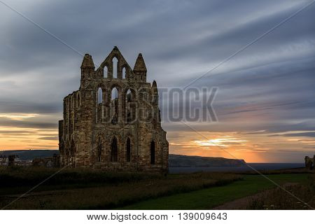 WHITBY ENGLAND - JULY 16: The ruins of Whitby Abbey against a sunset. In Whitby North Yorkshire England. On 16th July 2016.