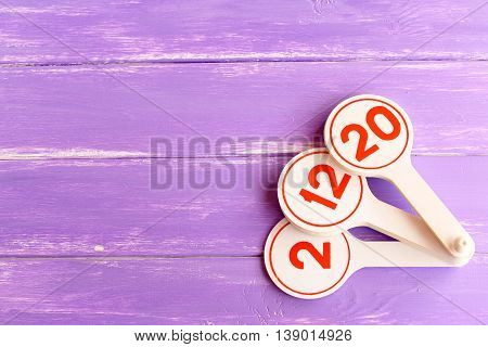 Educational toy to teach children numbers. Learning toy for kids on lilac wooden background with empty space for text. Teaching numbers to preschoolers fun
