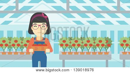 An asian female farmer holding a box with tomatoes on the background of greenhouse. Young farmer collecting tomatoes in the greenhouse. Vector flat design illustration. Horizontal layout.