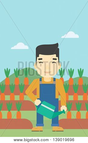 An asian farmer holding a watering can. Farmer watering carrots. Farmer standing on the background of carrots growing on field. Vertical layout.