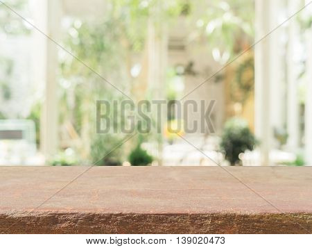 Stone board empty table in front of blurred background. Perspective brown stone over blur in coffee shop - can be used for display or montage mock up your products. vintage filtered image.