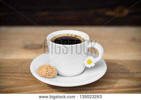 Cup of black coffee with biscotti arranged on wooden table