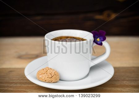 Cup of espresso coffee with biscotti arranged on wooden table