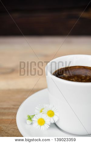 Cup of espresso coffee with daisy flower arranged on old rustic wooden table