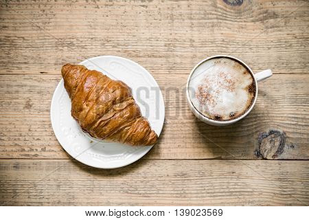 Cup of latte coffee with croissant on white plate arranged on old rustic wooden table. Top view