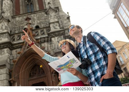 Have a look. Positive joyful smiling tourists holding city map and looking up while traveling