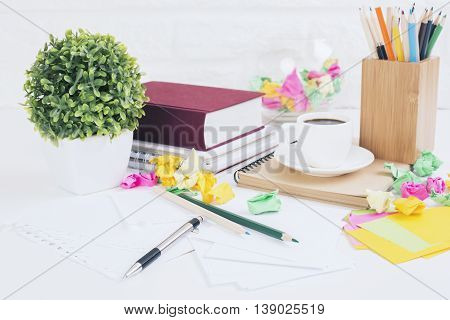 Closeup of messy office desktop with colorful crumpled paper balls coffee cup sationery items decorative plant book and other items on white brick wall background