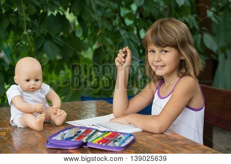 Girl makes lessons sitting at a table in the garden