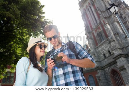 Have a look. Joyful delighted tourists standing outside and using photo camera while walking
