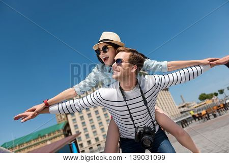 Just fly. Cheerful handsome smiling man holding his girlfriend on the back while having fun