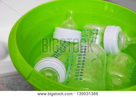Sterilizing baby bottles in plastic green basin