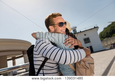 Missed you so much. Cheerful delighted nice couple embracing and standing outdoor while smiling