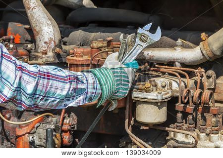 Man's hand with adjustable wrench near old diesel engine