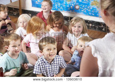 Montessori/Pre-School Klasse hören Lehrer auf Teppich