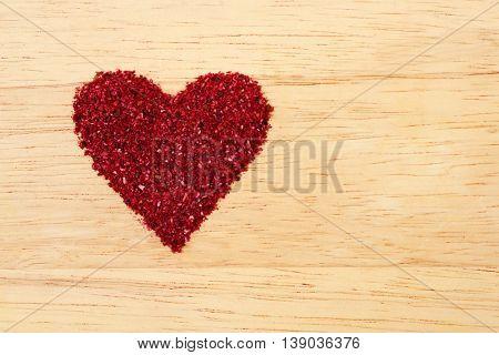 Heart shape heap of dried sumac on light wooden background