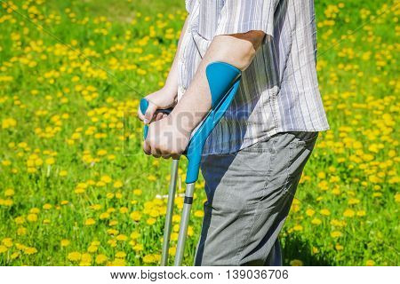 Disabled man with crutches on the dandelion field in summer
