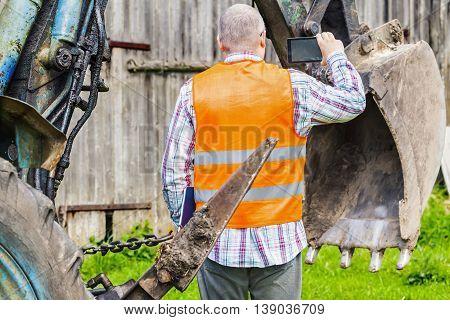 Worker filmed tractor's excavator scoop in summer day