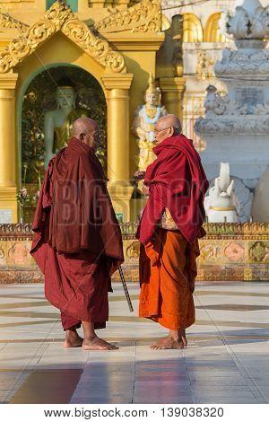 YANGON MYANMAR - FEBRUARY 01 2016: Unidentified Burmese monks in the buddhist costume visit the Shwedagon Pagoda. Shwedagon Pagoda is the most sacred Buddhist pagoda for the Burmese