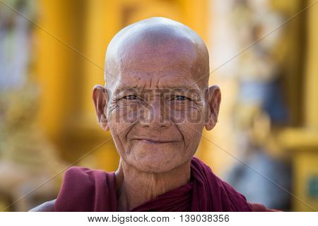 YANGON MYANMAR - FEBRUARY 01 2016: Unidentified portrait monk visit the Shwedagon Pagoda. Shwedagon Pagoda is the most sacred Buddhist pagoda for the Burmese