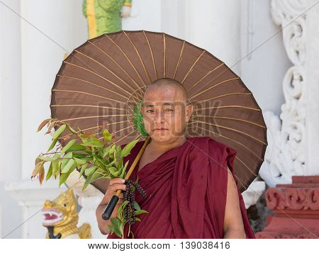 YANGON MYANMAR - FEBRUARY 01 2016: Unidentified Burmese monk in the buddhist costume visit the Shwedagon Pagoda. Shwedagon Pagoda is the most sacred Buddhist pagoda for the Burmese