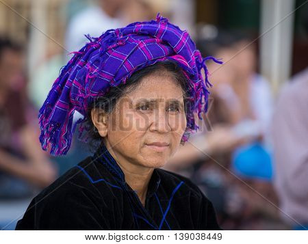 YANGON MYANMAR - FEBRUARY 01 2016: Unidentified Burmese woman in the national costume visit the Shwedagon Pagoda.The local people are hospitable and friendly to tourists