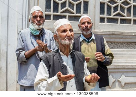 SRINAGAR INDIA - JUNE 11 2015: Unidentified Indian muslim men begging on the streets near the mosque in Srinagar Kashmir. India. Poverty is a major issue in India
