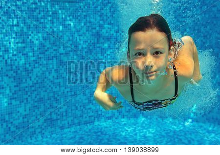 Child swims in pool underwater, happy active girl jumps, dives and has fun, kid sport on family vacation