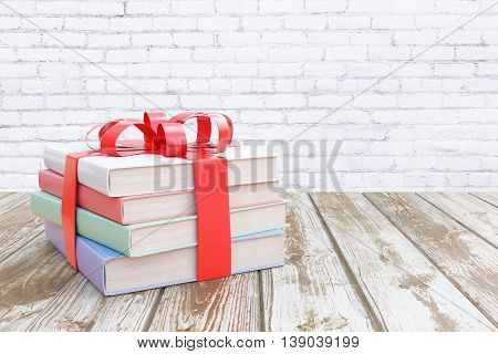 Aged wooden surface with stack of colorful book tied up with a ribbon as a present on white brick wall background. 3D Rendering