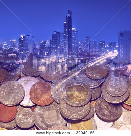 Double exposure of night city and group of international coins for finance concept