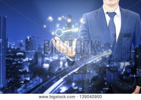 Double Exposure Of Businessman Showing Key Business To Sucess And City Center Background In Blue Ton