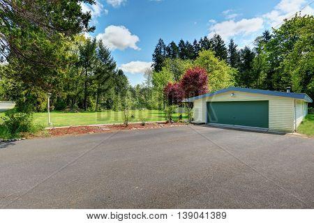 Wide Asphalt Driveway With Green Door Garage.