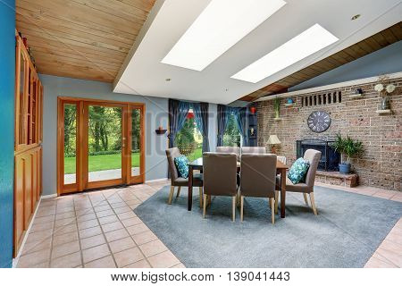 Light spacious dining room with stone tile wall and built-in fireplace skylight tile flooring and view of back yard. poster