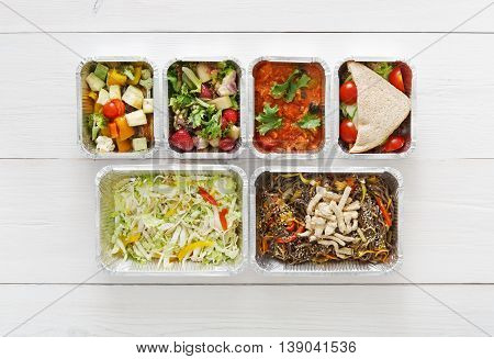 Healthy food delivery, daily ration. Take away of natural organic low carb diet. Fitness nutrition in foil boxes. Top view, flat lay with copy space at white wood